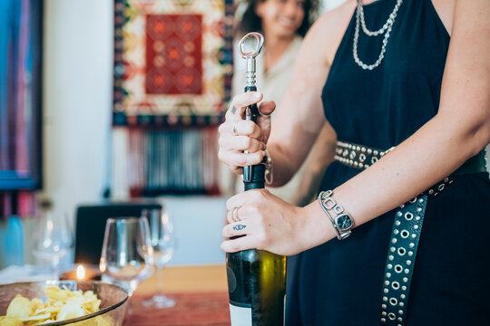 Woman opening wine bottle during social gathering at home