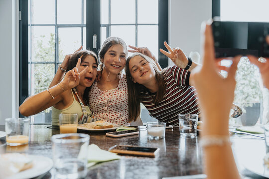 Group of teenage girls meeting for brunch, taking smartphone pictures