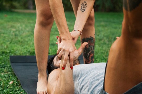 Couple holding hands while practicing acroyoga in park