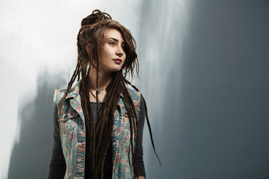 Hipster young woman with long dreadlocks standing against gray wall