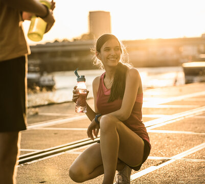 Smiling woman with friend holding water bottle while crouching outdoors