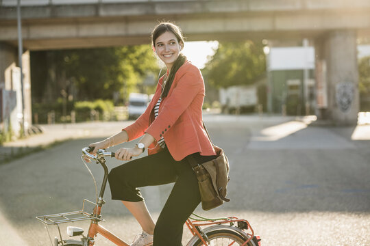 Smiling young woman riding bicycle on street in city