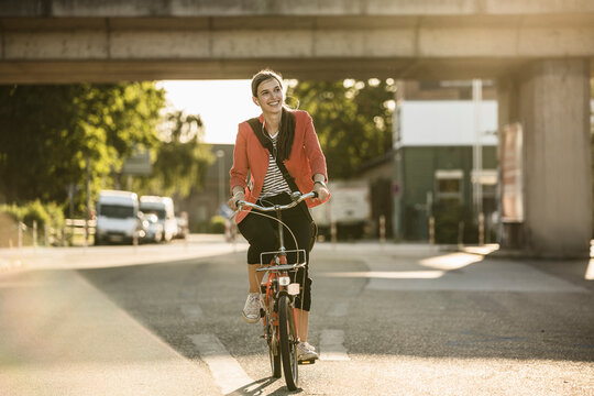 Happy young woman riding bicycle on street in city