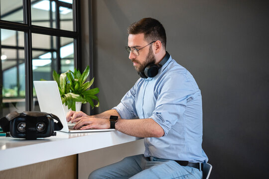 Confident businessman using laptop at desk in creative coworking office