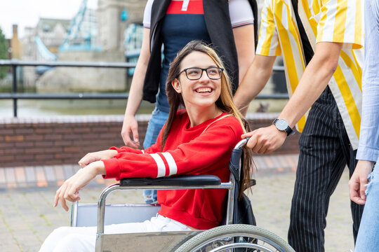 Smiling young woman on wheelchair enjoying weekend with friends in city