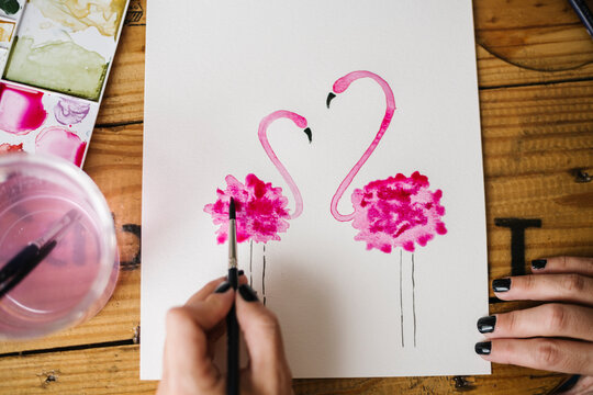 Close-up of woman hand painting flamingo animal on paper