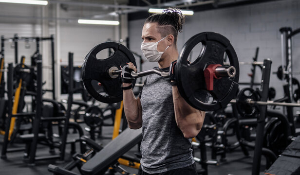 Pandemic gym - man working out with protective face mask during coronavirus outbreak