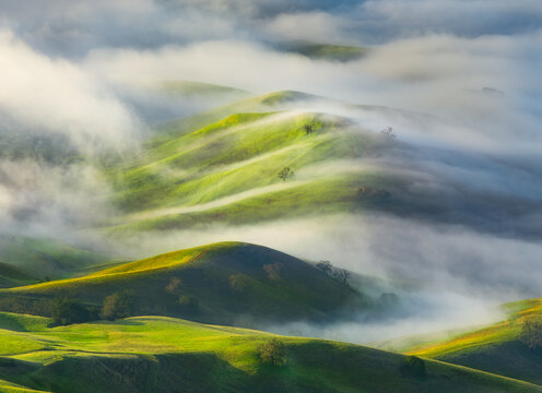 High angle view of fog over hills during sunrise