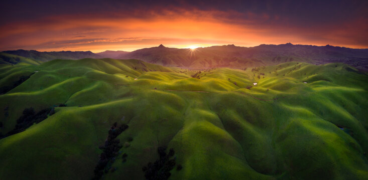 Scenic view of rolling hills in spring during sunset