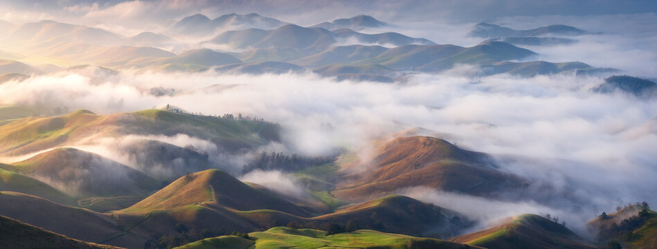Scenic view of hills covered with fog during sunrise