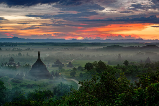 Scenic view of stupas on foggy landscape during sunset