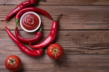 Red hot chili pepper. Sauce, tomatoes and pepper on a wooden background