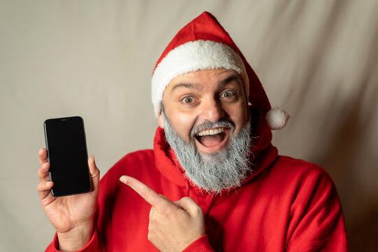Santa Claus points his finger at a cell phone and is delighted.