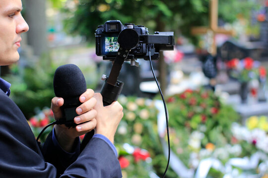 Elegant man in suit is recording grave with cross full of flowers. Funeral live streaming on cementary. Cameraman handing a microphone and camera on a gimbal.