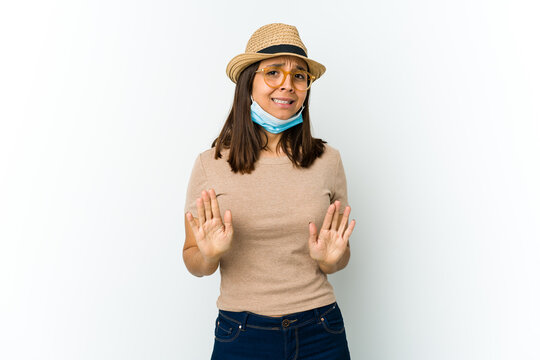 Young latin woman wearing hat and mask to protect from covid isolated on white background rejecting someone showing a gesture of disgust.