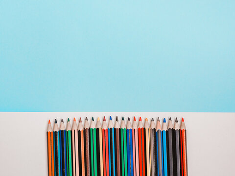 Multicolored rainbow color pencils on white and blue background