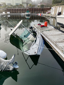 An aluminum fishing boat is sinking at it's slip on the dock, and is filling up with water quickly as it's automatic bailing system failed