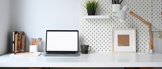 Mockup blank screen laptop and office supplies on white desk.