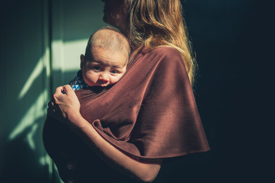 Young mother with her babyu in a sling is standing indoors