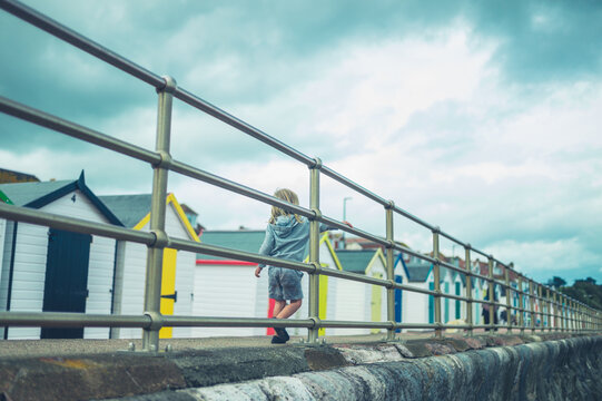Preschooler playing by railing on the beach in autumn