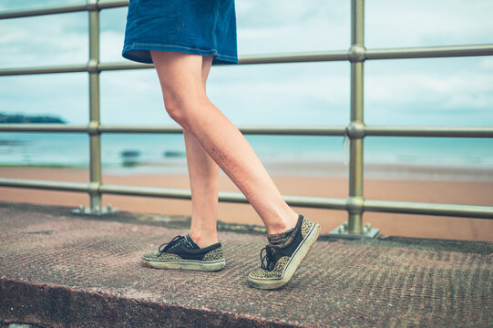 Legs of a young woman walking by railings on the beach
