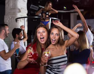 Smiling females friends with drinks dancing in the club on party