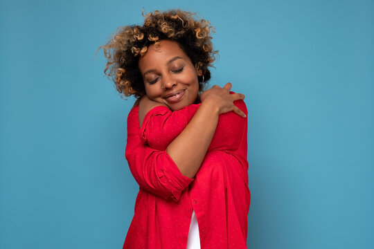African american woman with curly hair hugging herself