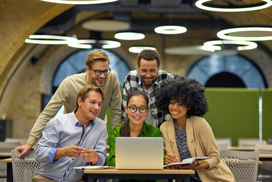 Group of young multiracial business people sitting at desk in the modern coworking space, looking at laptop screen and smiling, working together on a new project