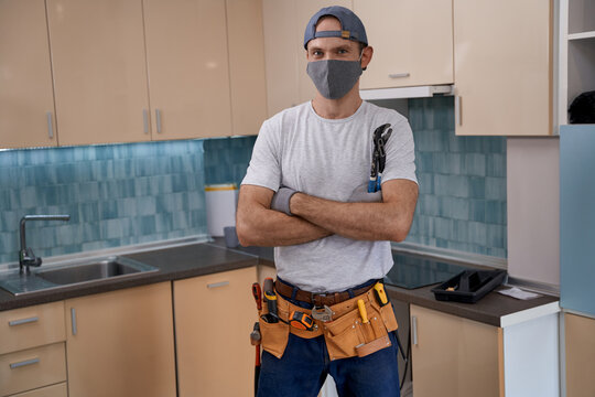 Young caucasian repairman in face mask working with furniture