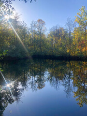 gorgeous sunbeams, autumn woods and and blue sky reflected in lake. Beautiful calming symmetry with copy space.