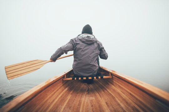 Rear view of man paddling canoe  in the winter