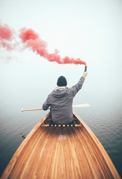 Man in canoe using smoke bomb to signal his position on the foggy lake