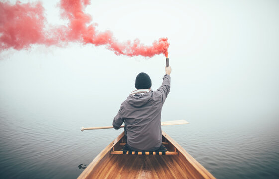 Canoeist using smoke bomb to signal his position on the foggy lake