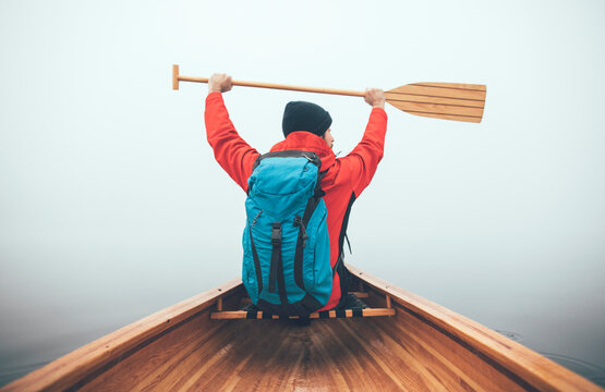Active man holds canoe paddle high