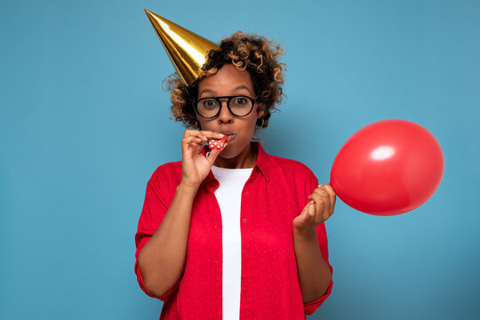 Amazed astonished african girl blowing up balloon preparing surprise for celebrating birthday