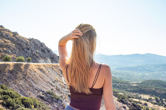 Young beautiful blonde woman looks at the horizon. The traveler stands in the mountains