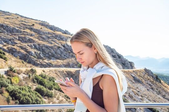 woman traveler using her mobile phone in the mountains