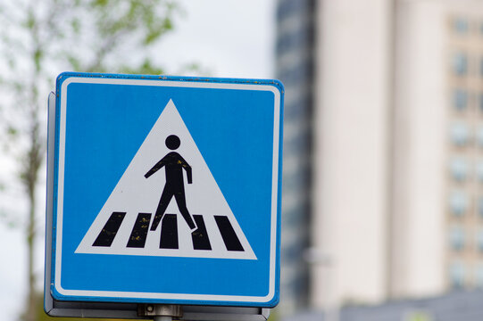 Blue pedestrian crossing sign with a building in the background in Arnhem, Netherlands