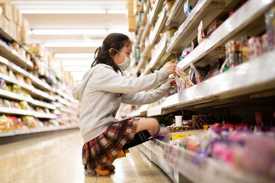 スーパーマーケットでお菓子を選ぶ女の子