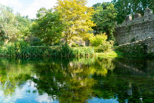 The river of the Garden of Ninfa, medieval stone bridge over the lake, relaxing view, Italy