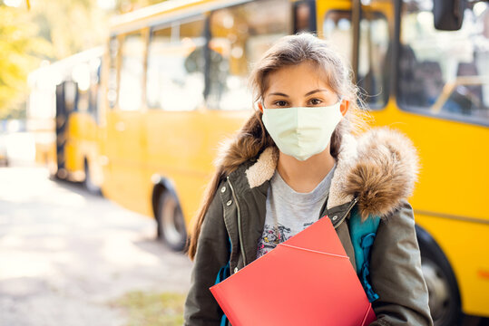 Secondary school girl learner in protective mask in front of school bus, ready to go home by bus. School education during the covid-19 pandemic