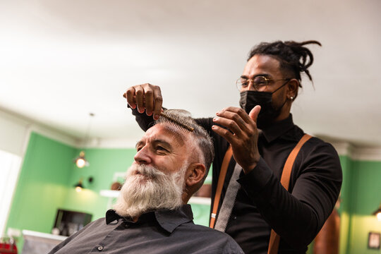 african american barber with mask coronavirus pandemic prevention comb white caucasian male with white beard