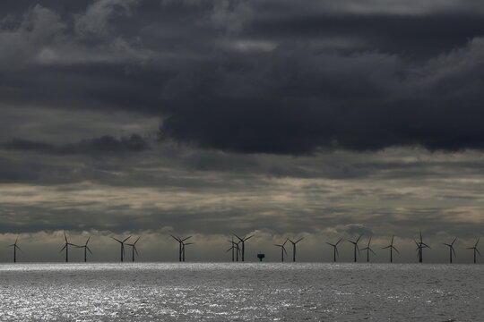 Rain clouds gather over an offshore wind farm off the coast of Finton-on Sea