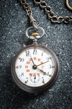 Vintage pocket watch on grey stone background 1