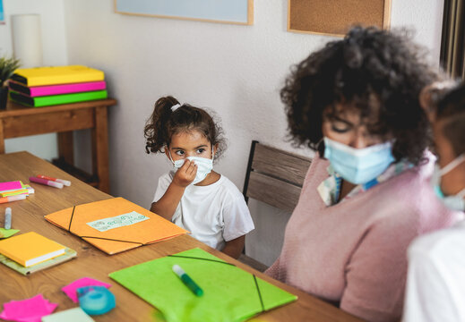 Small child puts on her surgical face mask - Teacher with children - School and safety measures for coronavirus