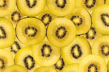 Fruity background composed of many golden kiwi slices