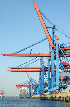 Harbor cranes and container vessel at the port in Hamburg, Germany