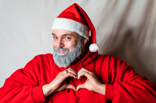 santa claus in the hoodie forms a heart with his hands in front of his chest and looks at the camera with a friendly smile