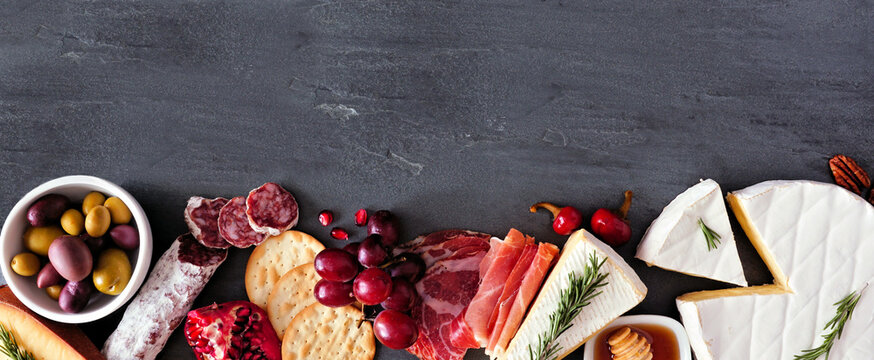 Assortment of cheese and meat appetizers. Top view bottom border on a slate stone banner background with copy space.
