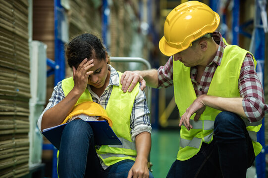Young African female warehouse worker staff feeling sad and stress while Caucasian man consoling and encouraging due to been fired from job cause by company bankruptcy from coronavirus pandemic.